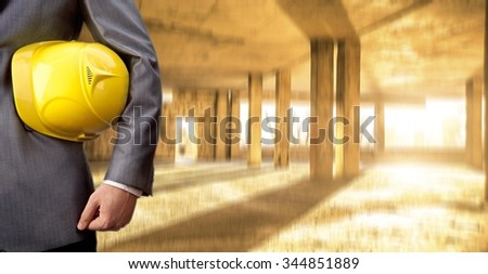 torso engineer or worker hand holding yellow helmet for workers against transparent glass office window perspective and sunset light with rays background Empty texture space for inscription - stock photo
