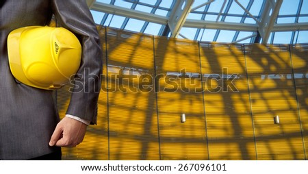 torso engineer or worker hand holding yellow helmet for workers security against blue transparent glass office window and sunset light with shadows background Empty texture space for inscription  - stock photo