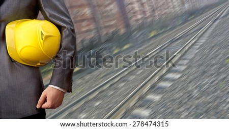 torso engineer or worker hand holding yellow helmet for workers security against the background of an railway with arc legs and rails for trolleys with coal in perspective Logistic idea concept  - stock photo