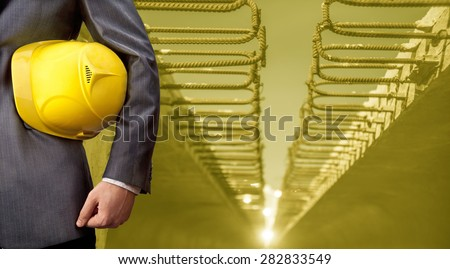 torso engineer or worker hand holding yellow helmet for workers security on concrete slab with reinforcement  background against sun light Copy Space for inscription Idea oe concept of safety - stock photo