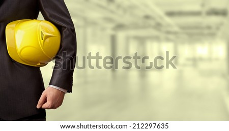 torso engineer or worker hand holding yellow helmet for workers security over empty old building inside concrete house background Copy Space for inscription Idea oe concept of safety - stock photo