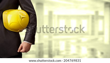 torso engineer or worker holding in hand yellow helmet for workers security over empty old building inside concrete house background Copy Space for inscription - stock photo