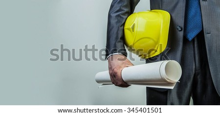 Torso engineer, worker or architect holding in hand blueprint and yellow plastic helmet hardhat on textured wall with gray wallpaper background Empty copy space for inscription