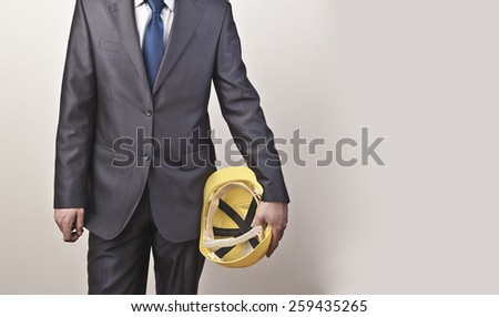 Torso engineer, worker or architect holding in hand yellow plastic helmet hardhat for security on textured wall with gray wallpaper background Empty copy space for inscription - stock photo