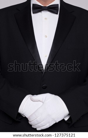 Torso of a man wearing a tuxedo with bow tie and white gloves.
