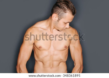 Torso of a tense man with perfect abdominal and chest muscles  - stock photo