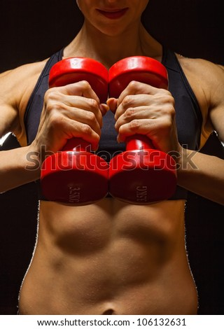 Torso of a young fit woman lifting dumbbells on dark background - stock photo