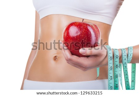 Torso of a young woman with an apple and meter isolated on white background - stock photo