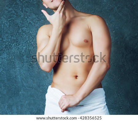 torso of an attractive young man with a towel after shower