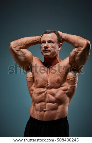 torso of attractive male body builder on gray background.