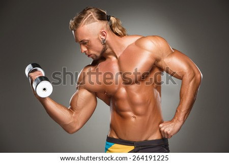 torso of attractive male body builder with dumbbell on gray background. - stock photo