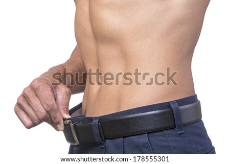 Torso of lean muscular Caucasian man pulling out belt line showing weightloss on white background - stock photo