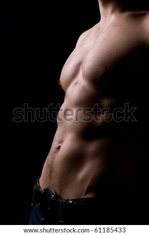 torso of strong athletic man on black - stock photo