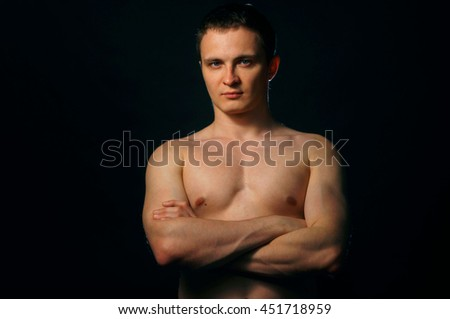 Torso of strong man against dark background