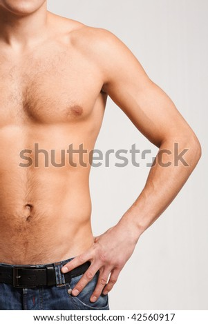 Torso of strong man in jeans with his arm on hip - stock photo