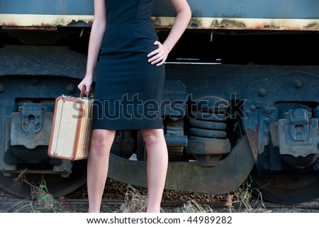 Torso of woman holding suitcase by train, hand on hip