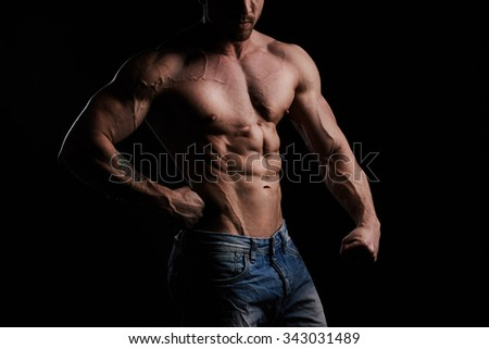 Torso of young muscular bodybuilder - stock photo