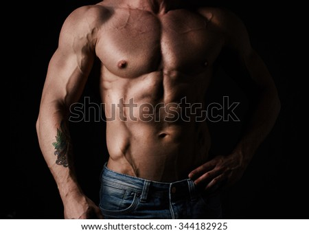 Torso of young muscular man wearing jeans - stock photo