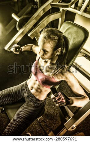 Torso portrait of Cheerful young adult caucasian woman working out on exercise machine inside gym dark room background Empty space for inscription Dramatic light in dusk - stock photo