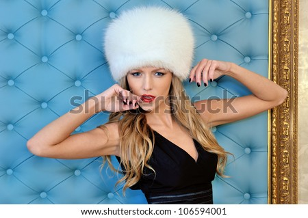 Torso portrait of the beautiful woman in white fur hat - stock photo