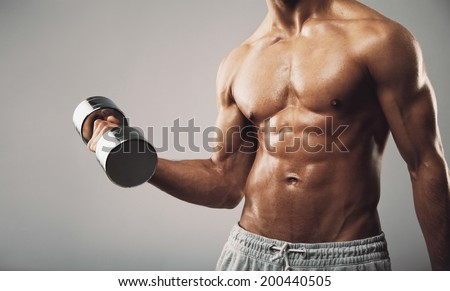 Torso shot of a young man with bare chest lifting dumbbells. Fit young man exercising with dumbbells on grey background. Cropped image of sweaty bodybuilder. - stock photo