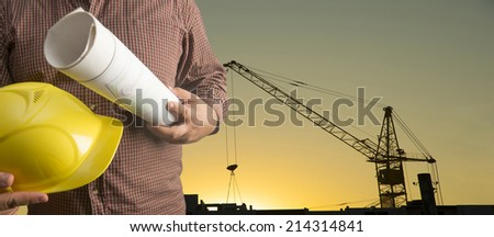torso worker or engineer hand holding yellow helmet and blueprint on background of new highrise apartment buildings and construction cranes on background of sunset sky Silhouette Crane lifts load - stock photo