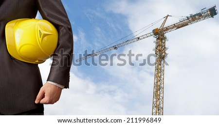 torso worker or engineer holding yellow helmet for workers security on background of new highrise apartment buildings and construction crane lifts load of  cloudy sky Empty copy space for inscription - stock photo