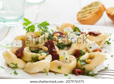 Tortellini Italian pasta topped with feta, basil, pine nuts and piquant tomatoes garnished with parsley and served with toasted grilled rolls - stock photo