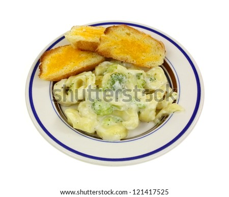 Tortellini pasta filled with cheese with a creamy alfredo broccoli sauce. - stock photo