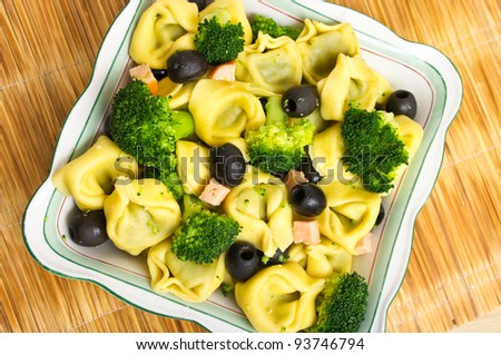 Tortellini salad with olives, salmon and broccoli