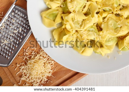 Tortellini stuffed with spinach and ricotta. Covered with grated cheese. - stock photo