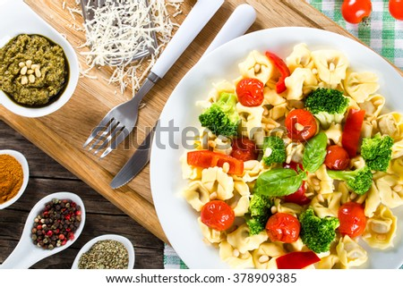 Tortellini with grilled cherry tomatoes, broccoli, red bell pepper and fried Pine nuts on a white dish with spice, sauce pesto and parmesan cheese on an old rustic table, italian style, top view
