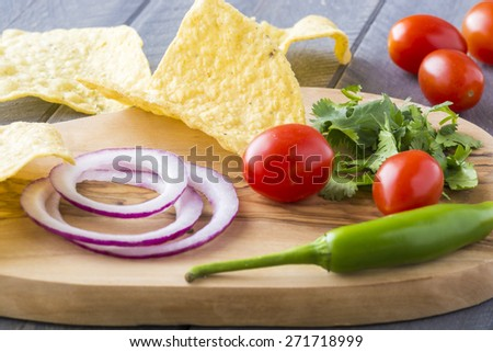 Tortilla chips and ingredients for dip on a wood.