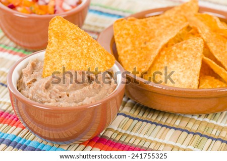 Tortilla Chips & Dips - Mexican totopos with refried beans and salsa.  - stock photo