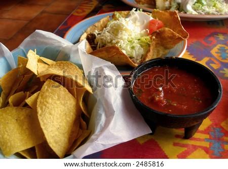 Tortilla chips, salsa, and taco salad at a Mexican restaurant. - stock photo