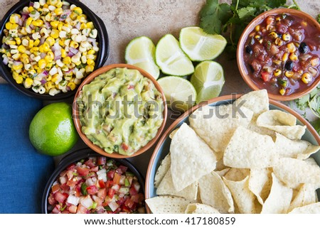Tortilla chips served with guacamole, salsa, and pico de gallo, view from above. - stock photo