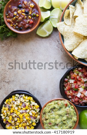 Tortilla chips served with guacamole, salsa, and pico de gallo with copy space, view from above.