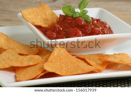 tortilla chips with a bowl of salsa dip