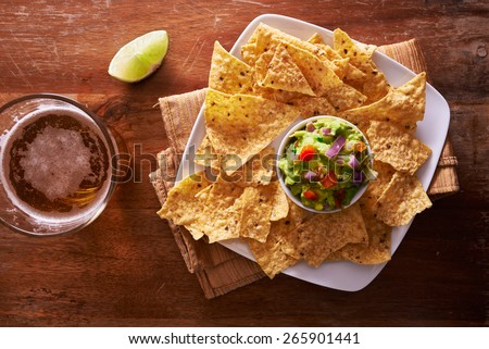 tortilla chips with guacamole and beer shot top down - stock photo