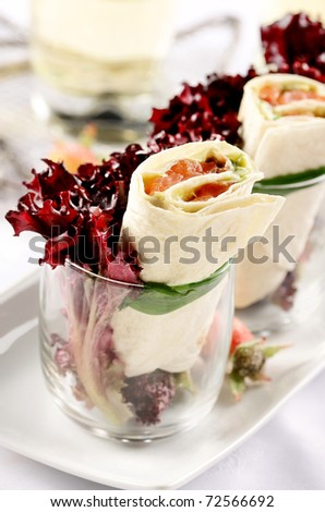 tortilla filled with smoked salmon cheese and vegetables garnished in glass with red salad - stock photo