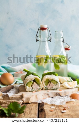 Tortilla rolls with cream cheese, turkey and vegetables on the wooden board. Two bottles of lemonade. - stock photo