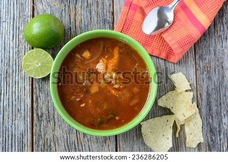 Tortilla Soup with Chips, fresh lime and spoon on Rustic Wood Background - stock photo