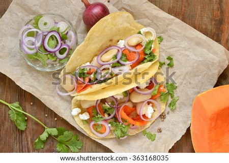 Tortilla, tacos with vegetables: pumpkin, white beans, goat cheese and onions, top view