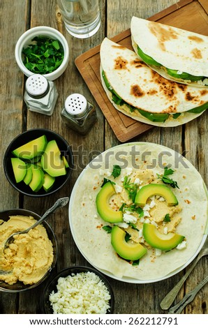 tortilla with hummus, avocado, feta and parsley on a dark wood background. tinting. selective focus - stock photo
