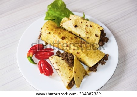 Tortilla with minced meat with chili and tomato on white plate - stock photo