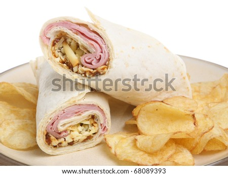 Tortilla wrap with ham, cheese & pickle and potato crisps. - stock photo