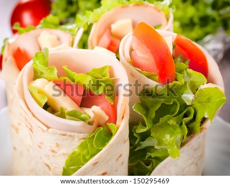 Tortilla wrap with turkey and vegetables. Selective focus in the middle of tortilla wrap - stock photo