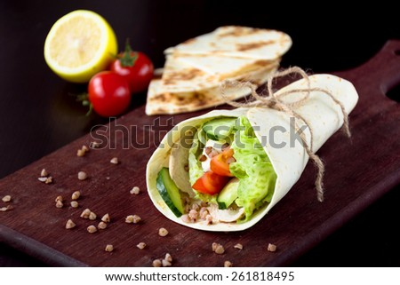 Tortilla wraps with fresh cucumber, tomatoes, lettuce leaf and grilled chicken breast on wooden cutting board. Healthy lunch, snack or light dinner meal - stock photo