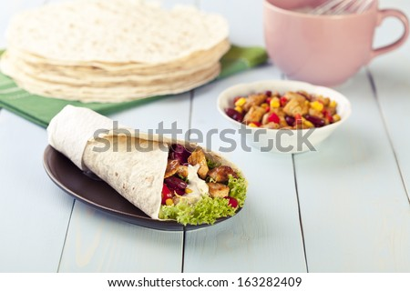 tortilla wraps with meat and vegetables on blue wood board