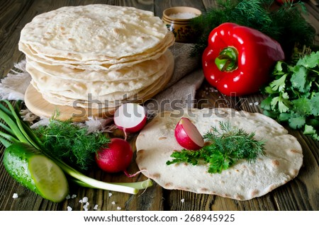 Tortilla wraps with vegetables. On the wooden table was a pile of pita - stock photo